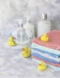 La pila di asciugamani con il bagno di gomma giallo ducks su fondo di marmo bianco, spazio per testo, fuoco selettivo Fotografie Stock