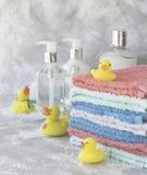 La pila di asciugamani con il bagno di gomma giallo ducks su fondo di marmo bianco, spazio per testo, fuoco selettivo Immagini Stock Libere da Diritti