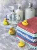 La pila di asciugamani con il bagno di gomma giallo ducks su fondo di marmo bianco, spazio per testo, fuoco selettivo Fotografia Stock Libera da Diritti
