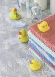 La pila di asciugamani con il bagno di gomma giallo ducks su fondo di marmo bianco, spazio per testo, fuoco selettivo Fotografia Stock