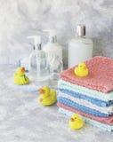 La pila di asciugamani con il bagno di gomma giallo ducks su fondo di marmo bianco, spazio per testo, fuoco selettivo Immagini Stock