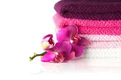 La pila di asciugamani di bagno variopinti e di orchidea porpora fiorisce immagini stock libere da diritti