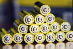 La pila di batterie AA gialle si chiude sul fondo astratto di colore Fotografia Stock