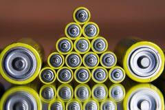 La pila di batterie AA gialle si chiude sul fondo astratto di colore Fotografie Stock Libere da Diritti
