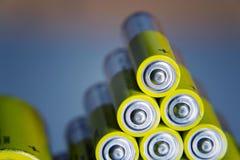 La pila di batterie AA gialle si chiude sul fondo astratto di colore Fotografia Stock Libera da Diritti
