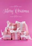 La pila di bello regalo rosa del pois presenta con il Buon Natale che accoglie Fotografia Stock