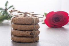 La pila di biscotti, cordicella di perevyazanaya, si trova accanto ad una rosa rossa Fondo vago, bokeh Immagine romantica, prima  Fotografia Stock Libera da Diritti