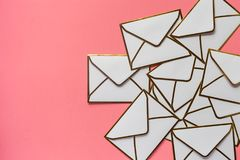 La pila di buste bianche con le creste dorate sopra arrossisce backgr rosa Fotografie Stock