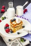La pila di cuore ha modellato i pancake con le bacche fresche Immagine Stock