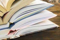 La pila di libro con copertina rigida aperta prenota su una vecchia tavola di legno di marrone scuro Istruzione fotografia stock
