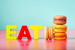 La pila di macarons sopra con mangia i caratteri in grassetto Fotografie Stock
