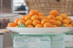 La pila di piccole arance fruttifica sul piatto bianco per la prima colazione di mattina Fotografia Stock