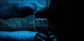 La pila di vestiti piegati, blue jeans ansima, pantaloni blu scuro del denim su fondo scuro Immagini Stock