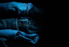 La pila di vestiti piegati, blue jeans ansima, pantaloni blu scuro del denim su fondo scuro Fotografia Stock