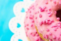 La pile de beignets vitrés de rose avec du sucre arrose sur le support de gâteau blanc avec des coeurs, fond bleu-clair, copyspac Image stock