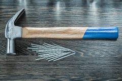 La pile de construction cloue le marteau de griffe sur le conseil en bois photographie stock libre de droits