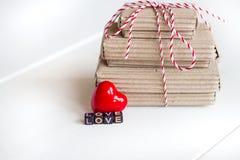 La pile de handcraft des boîte-cadeau sur le fond en bois blanc avec amour rouge de coeur et de textes des cubes colorés Copiez l Photo stock