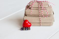 La pile de handcraft des boîte-cadeau sur le fond en bois blanc avec amour rouge de coeur et de textes des cubes colorés Copiez l Image libre de droits