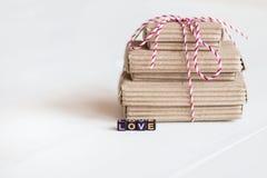 La pile de handcraft des boîte-cadeau sur le fond en bois blanc avec amour des textes des cubes colorés Copiez l'espace, le place Photographie stock libre de droits