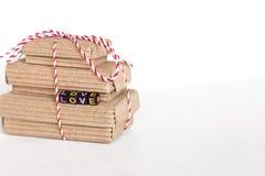 La pile de handcraft des boîte-cadeau sur le fond en bois blanc avec amour des textes des cubes colorés Copiez l'espace, le place Photographie stock