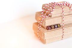 La pile de handcraft des boîte-cadeau sur le fond en bois blanc avec amour des textes des cubes colorés Copiez l'espace, le place Image libre de droits
