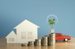 La pile de l'argent invente avec la maison de petit arbre vert, d'ampoule, de voiture de jouet et de papier, sur le fond bleu en  image libre de droits