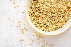 La pile de la farine d'avoine s'écaille dans une cuvette Image stock