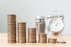 La pile de pièce de monnaie intensifient l'augmentation épargnent l'argent avec l'horloge et le ja brouillés Photos libres de droits