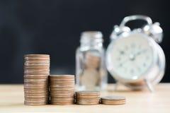 La pile de pièce de monnaie intensifient l'augmentation épargnent l'argent avec l'horloge et le ja brouillés Images libres de droits