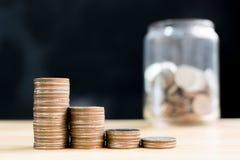 La pile de pièce de monnaie intensifient l'augmentation épargnent l'argent avec le backgrou brouillé de pot Images stock