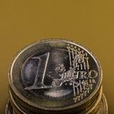 La pile de pièces de monnaie est d'un euro encaissez l'euro corde de note d'argent de l'orientation cent des euro cinq Fond foncé Photo libre de droits