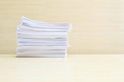 La pile de plan rapproché du papier de travail sur le bureau et le mur en bois brouillés a donné au fond une consistance rugueuse Photo libre de droits
