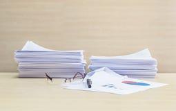 La pile de plan rapproché du papier, des verres et du stylo de travail sur le bureau et le mur en bois brouillés a donné au fond  Photographie stock