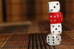 La pile de plastique de trois blancs découpe et une matrice rouge sur le fond brun de conseil en bois Six cubes en côtés avec les Photo libre de droits