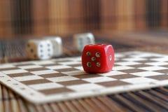 La pile de plastique de trois blancs découpe et une matrice rouge sur le fond brun de conseil en bois Six cubes en côtés avec les Photo stock