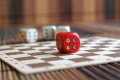 La pile de plastique de trois blancs découpe et une matrice rouge sur le fond brun de conseil en bois Six cubes en côtés avec les Images libres de droits