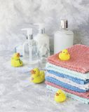La pile de serviettes avec le bain en caoutchouc jaune se penche sur le fond de marbre blanc, l'espace pour le texte, foyer sélec Images stock