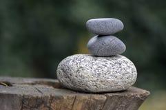 La pile de trois pierres de zen sur les cailloux de tronçon, blancs et gris en bois de méditation dominent Photo libre de droits