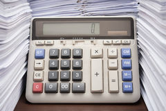 La pile des documents sur le bureau empilent haut avec la calculatrice Images stock