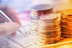 La pile des pièces de monnaie et d'une main tenant un stylo bille examine un diagramme technique d'instrument financier Photographie stock
