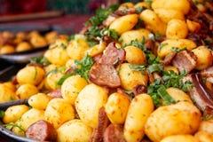La pile des pommes de terre cuites s'est mélangée à la saucisse et au persil européens grillés Nourriture de rue photos stock