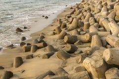 la pile des tetrapods concrets gris dépassent de l'à sable jaune humide Barrière de tsunami photos libres de droits