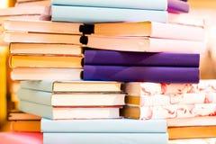 La pile lumineuse de livres beaucoup sont dans un substrat de pile, mélangé et coloré de fond Image stock