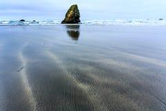 La pile solitaire de mer se lève du sable sur la plage abandonnée pendant la marée basse Photos stock