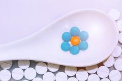 La pillola è disposta in un cucchiaio bianco immagine stock