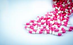 La pilule de rose et blanche de capsules s'est renvers?e du conteneur en plastique blanc de bouteille concept global de soins de  photo stock