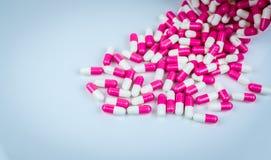 La pilule de rose et blanche de capsules s'est renvers?e du conteneur en plastique blanc de bouteille concept global de soins de  images stock