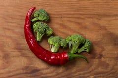 La pimienta de chile rojo con bróculi ramifica en el escritorio de madera Imágenes de archivo libres de regalías