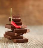 La pimienta de chile rojo en pila de chocolate oscuro junta las piezas Foto de archivo