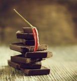 La pimienta de chile rojo en pila de chocolate oscuro junta las piezas Foto de archivo libre de regalías